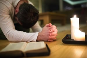 Man praying with a bible and candle